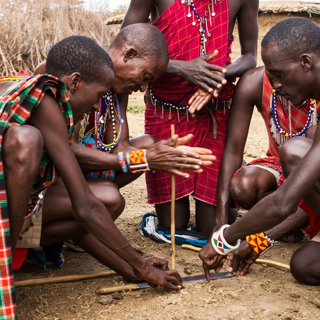 maasai men trying to start a fire tanzania kenya